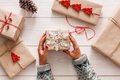 O ` s da mulher entrega o envolvimento do feriado do Natal atual com guita do ofício fotografia de stock