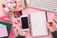 O ` s da mulher entrega a escrita no bloco de notas e no smartphone espirais da terra arrendada Fotos de Stock Royalty Free