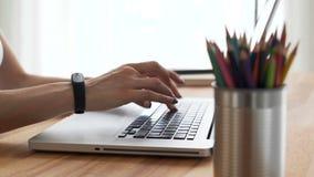 O ` s da mulher entrega a escrita no desktop no espaço de trabalho filme