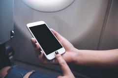 O ` s da mulher entrega guardar e apontar em um telefone esperto branco com a tela preta vazia do desktop ao lado de uma janela d imagens de stock