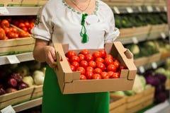 O ` s da mulher entrega guardar uma caixa grande da colheita do tomate no mercado Fotografia de Stock Royalty Free