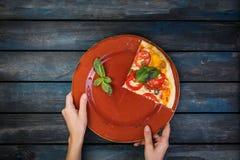 O ` s da mulher entrega guardar uma placa com uma parte de margarita da pizza com fatias do tomate, azeitonas e folhas da manjeri Imagens de Stock