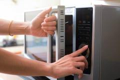 O ` s da mulher entrega a micro-ondas de fechamento Oven Door And Preparing Food dentro imagens de stock royalty free