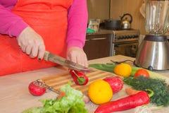 O ` s da mulher entrega a pimenta do corte, atrás dos legumes frescos Cozinheiro da mulher na cozinha O cozinheiro chefe corta os Foto de Stock