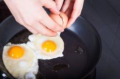O ` s da mulher entrega a quebra quebrando ovos na fritura para o Br do ` s de domingo Imagem de Stock