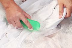 O ` s da mulher entrega a roupa branca de lavagem da cor na bacia foto de stock royalty free