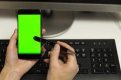 O ` s das mulheres entrega a tela do telefone dos toques com a pena para o écran sensível mob fotos de stock royalty free