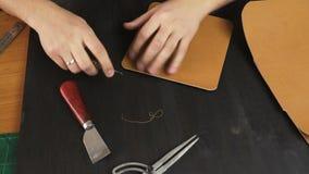 O ` s do artesão entrega o trabalho com uma parte de couro na tabela video estoque