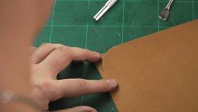 O ` s do artesão entrega o trabalho com uma parte de couro na tabela filme