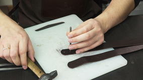 O ` s do artesão entrega o trabalho com uma parte de couro na tabela vídeos de arquivo