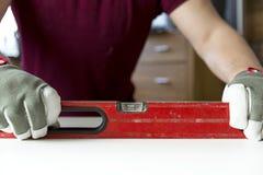 O ` s do carpinteiro entrega a verificação ao nível da tabela de madeira em casa Projetos de DIY, trabalhador manual imagem de stock royalty free