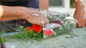 O ` s do florista da mulher entrega a fatura do ramalhete com as rosas na tabela para o florista filme