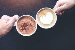 O ` s do homem e da mulher entrega guardar copos do café e do chocolate quente com fundo de madeira da tabela Fotografia de Stock Royalty Free