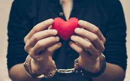 O ` s do homem entrega salvar como um coração vermelho junto com punhos da mão foto de stock royalty free