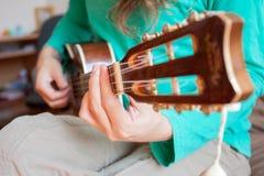 O ` s do homem novo entrega o jogo de uma uquelele da guitarra acústica na casa Um homem que joga a uquelele no fim acima da vist foto de stock