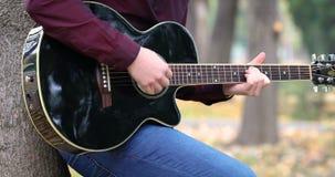 O ` s do homem novo entrega o jogo do músico do artista da guitarra acústica fora video estoque