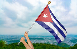 O ` s do homem novo entrega orgulhosamente a ondulação da Cuba bandeira nacional no céu, rendição da parte 3D Fotografia de Stock