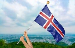 O ` s do homem novo entrega orgulhosamente a ondulação da Islândia bandeira nacional no céu, rendição da parte 3D Foto de Stock Royalty Free