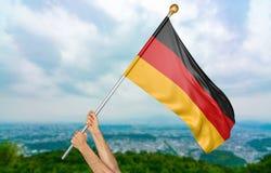 O ` s do homem novo entrega orgulhosamente a ondulação de Alemanha bandeira nacional no céu, rendição da parte 3D Foto de Stock Royalty Free