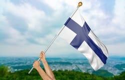 O ` s do homem novo entrega orgulhosamente a ondulação de Finlandia bandeira nacional no céu, rendição da parte 3D Imagens de Stock Royalty Free