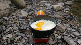 O ` s dos homens entrega ovos fritos de sal em uma frigideira em um acampamento video estoque
