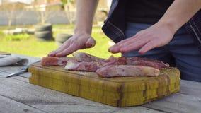 O ` s dos homens entrega o sal e salpica a carne Preparação para um assado filme