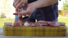 O ` s dos homens entrega o sal e salpica a carne Preparação para um assado vídeos de arquivo