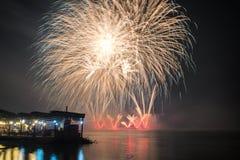 O ` s Eve Fireworks do ano novo lançou-se da água com reflexões imagens de stock royalty free