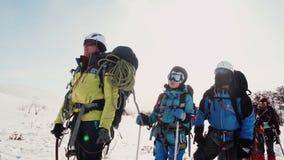 O s?nior da equipe dos montanhistas mostra o sentido da m?o do trajeto com uma picareta de gelo a equipe escuta-lhe vídeos de arquivo