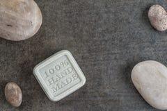 O sabão feito a mão com as pedras no fundo preto, o produto dos cosméticos e o corpo importam-se Fotos de Stock Royalty Free