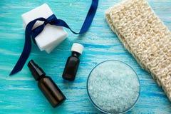 O sabão orgânico natural engarrafa a bucha orgânica do óleo essencial e do sal do mar em uma tabela de madeira azul Imagens de Stock