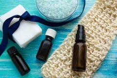 O sabão orgânico natural engarrafa a bucha orgânica do óleo essencial e do sal do mar em uma tabela de madeira azul Foto de Stock