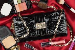 O saco bonito do couro envernizado e dos cosméticos que encontram-se no vermelho sentou-se imagens de stock royalty free