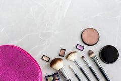 O saco cosmético, escovas, cora, as sombras para os olhos, bronzer em uma superfície do mármore imagens de stock