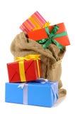 O saco da meia encheu-se com os lotes dos presentes do Natal isolados no fundo branco Fotografia de Stock Royalty Free
