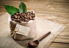 O saco da serapilheira encheu-se com os feijões de café no fundo de madeira imagem de stock royalty free