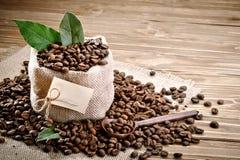 O saco da serapilheira encheu-se com os feijões de café no fundo de madeira foto de stock royalty free
