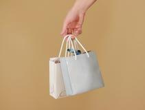 O saco de papel do presente da placa dois com corações zomba acima de guardar à disposição em Fotografia de Stock Royalty Free