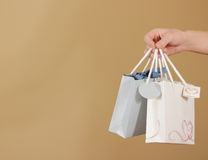 O saco de papel do presente da placa dois com corações zomba acima de guardar à disposição em Fotografia de Stock