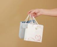 O saco de papel do presente da placa dois com corações zomba acima de guardar à disposição em Fotos de Stock Royalty Free