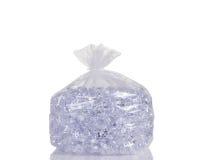 O saco de plástico claro encheu-se com os cubos de gelo isolados no backgr branco imagens de stock royalty free
