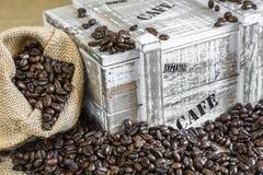 O saco de serapilheira encheu-se com os feijões de café ao lado da caixa de madeira velha Foto de Stock