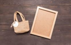 O saco do saco da juta com etiqueta e a moldura para retrato estão nos vagabundos de madeira Imagem de Stock