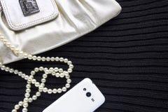 O saco, os grânulos e o telefone do ` s das mulheres no preto fizeram malha a tela O fundo Fotografia de Stock Royalty Free