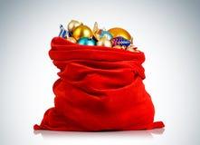 O saco vermelho de Santa Claus com Natal brinca no fundo Fotos de Stock
