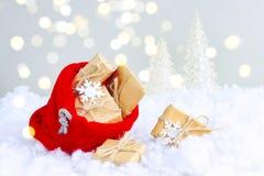 O saco vermelho do Natal com caixa de presente encontra-se na neve Fotografia de Stock