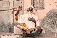 O sadhu indiano velho fala acima dos scriptures sagrados fotografia de stock royalty free