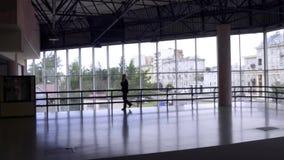O salão vazio grande com teto alto aonde o homem anda no terno escuro fala no telefone filme