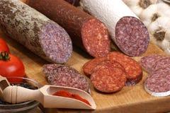 O Salami e o salami das fatias em uma madeira embarcam Imagens de Stock