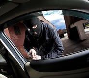 O salteador e o ladrão em uma máscara sequestram o carro foto de stock